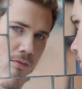 Blone hair blue eyed man looking at his reflection in mirror